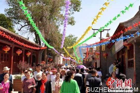 6月9日,兰州市西固区第三届文化旅游节暨河口古镇招商推介会在河口古镇举行。图为河口镇街道上游人如织。郭炯摄
